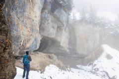 Hiker Below Waterfall in Snow